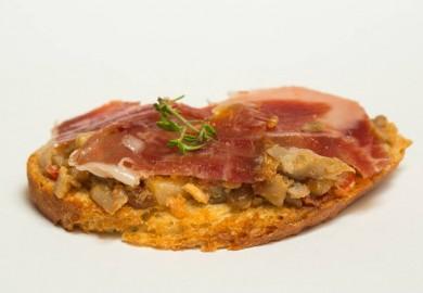 """Tapa """"Montañera"""": Pan sable, setas, almendras molidas, ajo, tomillo, tomate y jamón ibérico de bellota. Origen: Andalucía y Extremadura  EL PALADAR DE LAVAPIÉS – C/ Argumosa, 5"""
